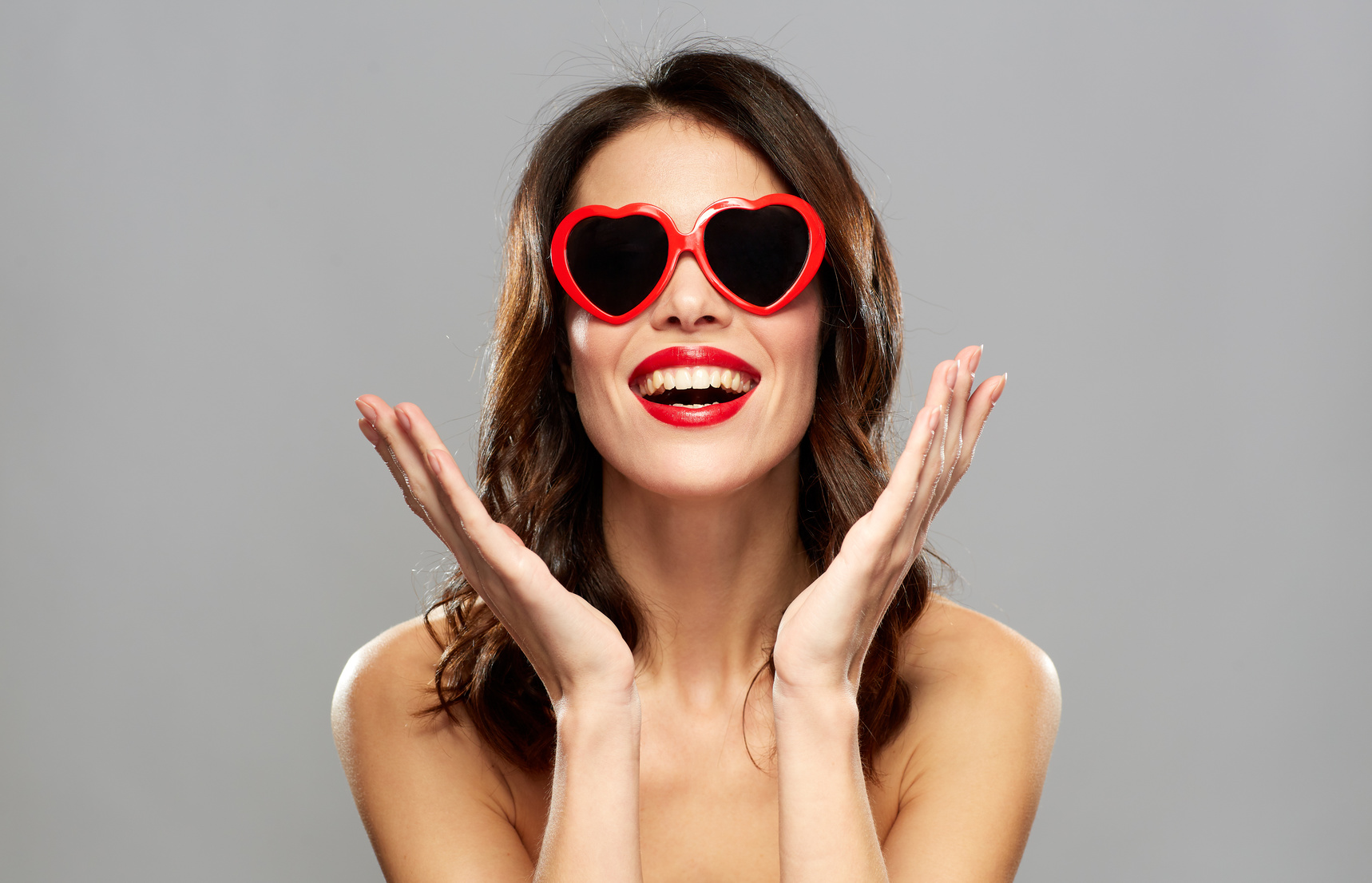 valentines day, beauty and people concept - happy smiling young woman with red lipstick and heart shaped sunglasses over gray background
